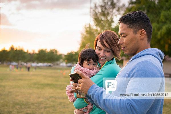 Paar mit Baby  mit Mobiltelefon im Park