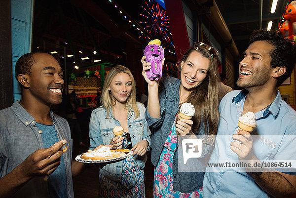Adult friends eating ice creams in amusement park at night  Santa Monica  California  USA