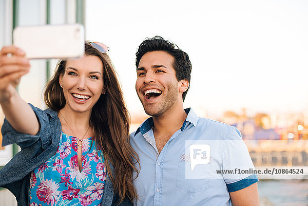 Young couple taking smartphone selfie on pier  Santa Monica  California  USA