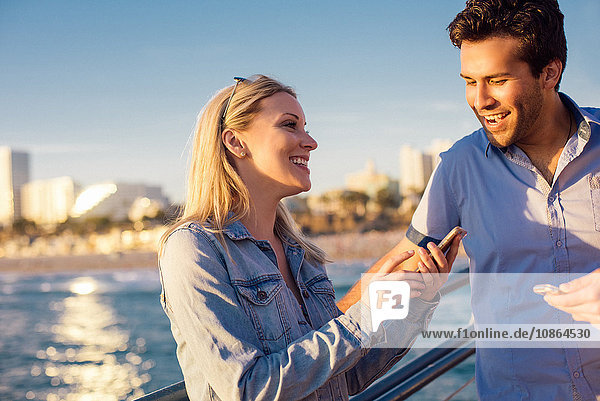 Junges Paar liest Smartphone-Text am Pier  Santa Monica  Kalifornien  USA