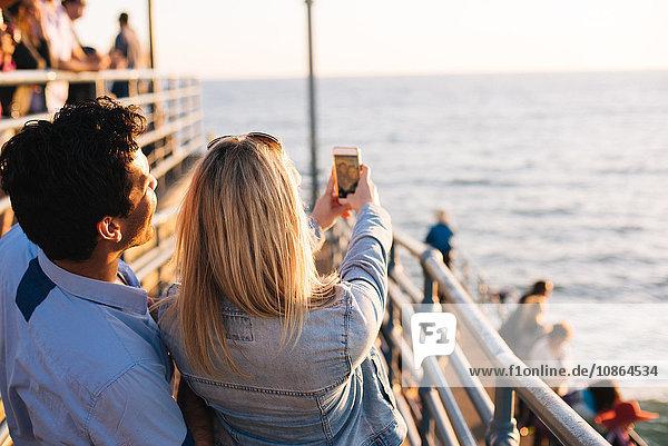 Rückansicht eines jungen Paares auf dem Pier  das sich ein Smartphone-Selfie nimmt  Santa Monica  Kalifornien  USA
