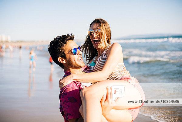 Young man carrying girlfriend on beach  Santa Monica  California  USA
