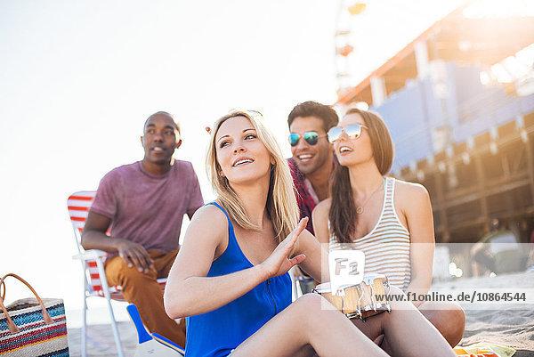 Young woman with friends bongo drumming on beach  Santa Monica  California  USA