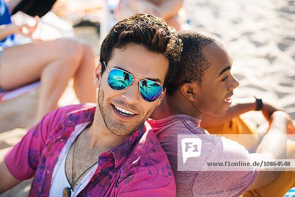 Portrait of two men sitting back to back on beach  Santa Monica  California  USA