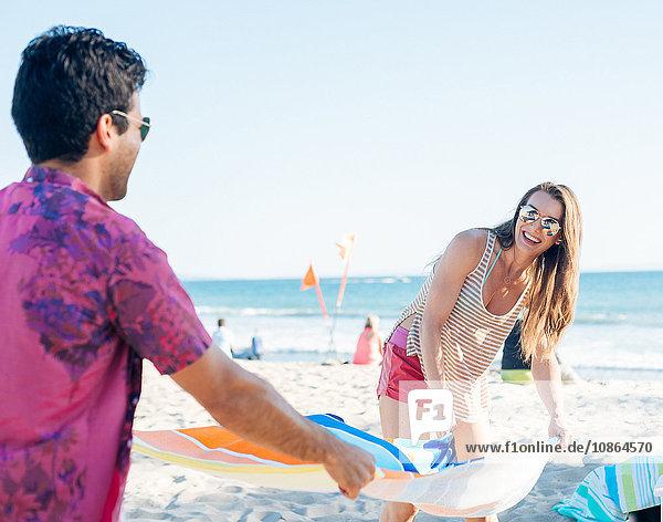 Junges Paar bereitet Strandtuch am Strand vor  Santa Monica  Kalifornien  USA