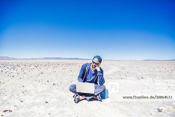 Mann sitzt im Schneidersitz in der Wüste und sucht auf Laptop  Nevada  USA