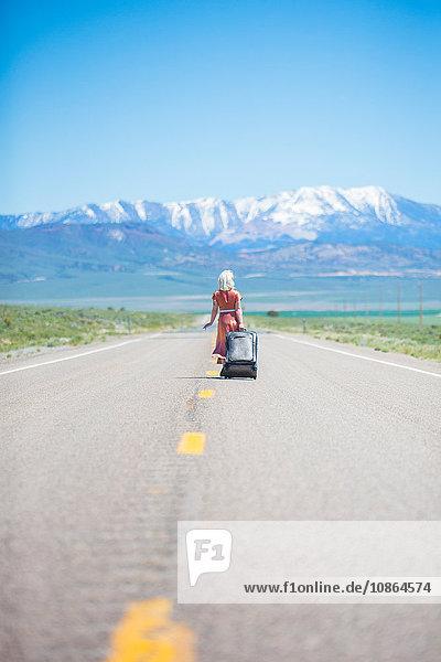 Rückansicht einer jungen Frau im Stil der 1950er Jahre  die allein auf dem Highway 50 geht und einen Rollkoffer zieht  Nevada  USA