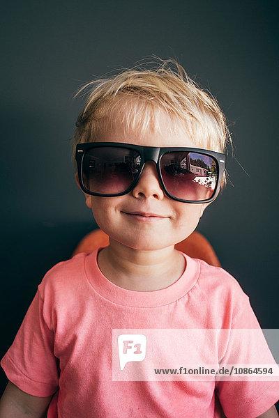 Studioporträt eines süßen Jungen mit übergroßer Sonnenbrille