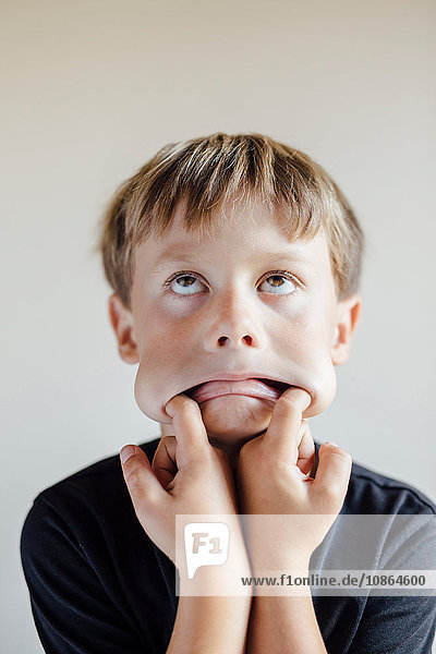 Studioporträt eines Jungen,  der mit den Fingern im Mund am Gesicht zieht