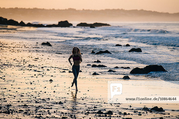 Silhouetted female runner running at sunset on beach  Los Angeles  California  USA