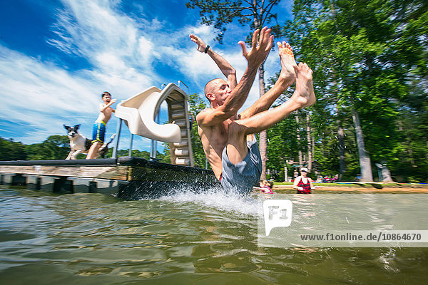 Mann,  der am Jackson Lake,  Georgia,  USA,  von einem Molenrutsch in den See gespritzt ist