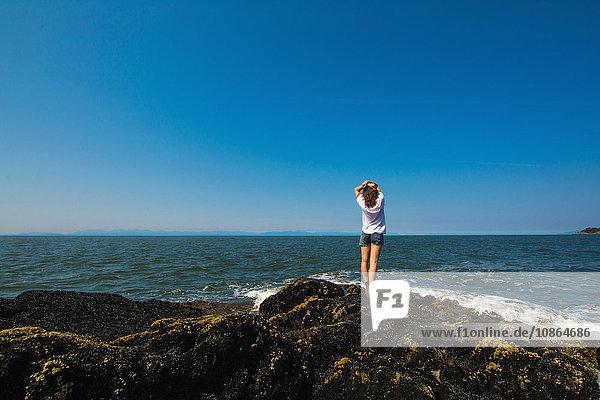 Junge Frau steht auf Felsen am Ozean  Bowen Island  Britisch-Kolumbien  Kanada