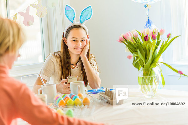 Teenage girl and brother at table dyeing hard boiled eggs for Easter