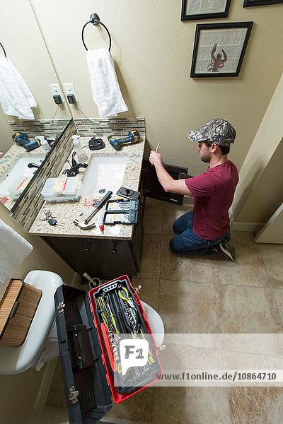 Man with toolbox kneeling to repair bathroom