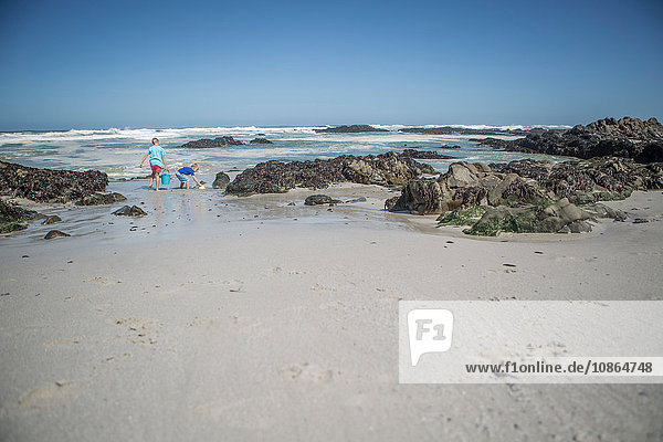 Two boys playing with buckets on beach  Cape Town  South Africa
