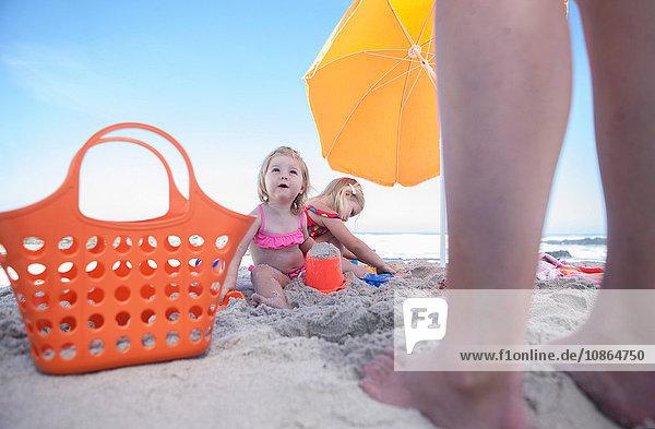 Zwei Schwestern am Strand sitzend  Vaters Beine  Kapstadt  Südafrika