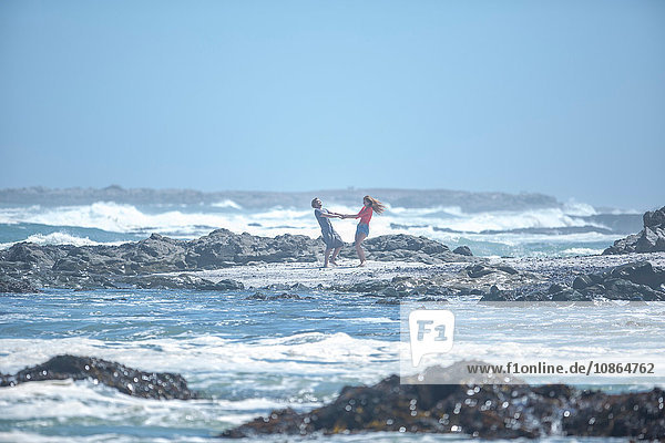 Distant view of young couple holding hands and spinning each other around on beach  Cape Town  South Africa