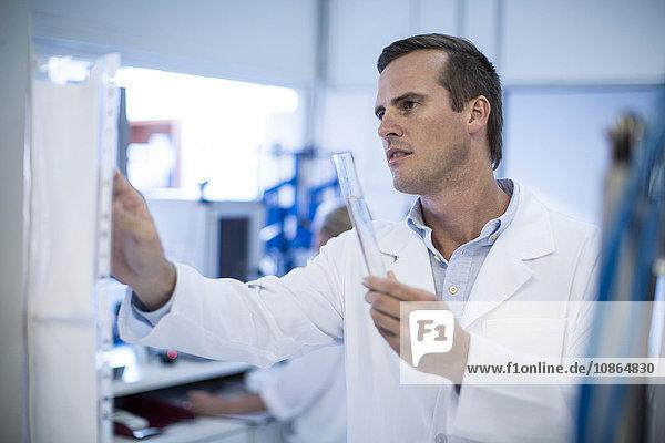 Mid adult man adjusting laboratory equipment  holding test tube