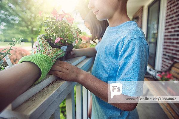 Hand wearing gardening glove handing plant to boy and girl