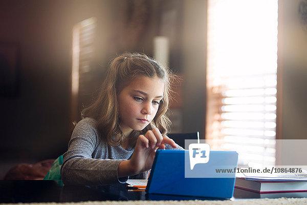 Girl at desk using digital tablet