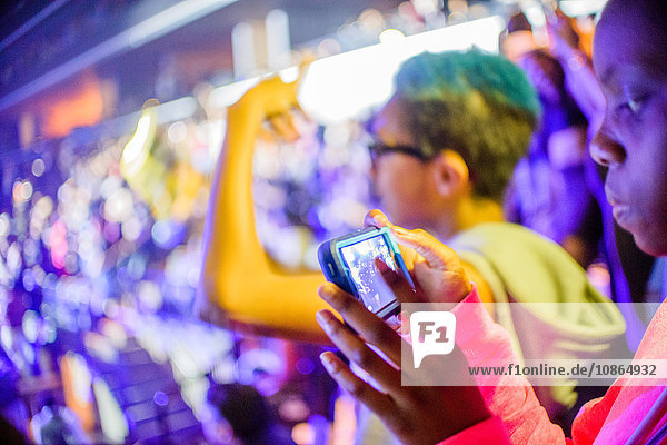 Teenage girl looking at smartphone at fairground stall at night  Brooklyn  USA