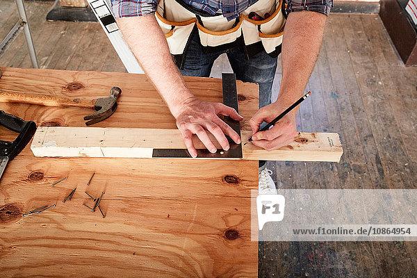 Schrägansicht eines Zimmermanns  der Holz mit dem gesetzten Quadrat markiert