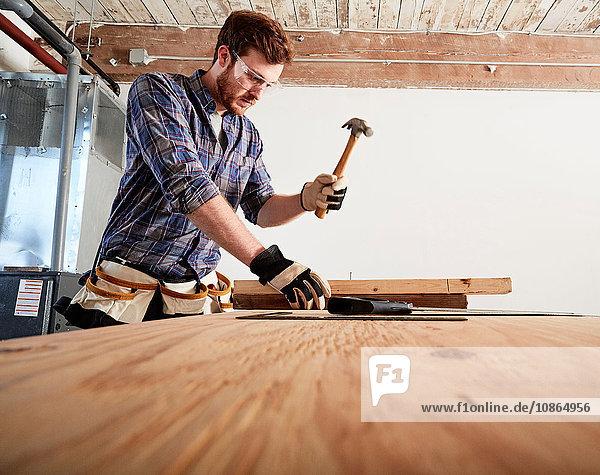 Schreiner in der Werkstatt mit Hammer