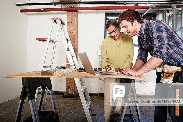 Zimmermann und Kunde mit Laptop