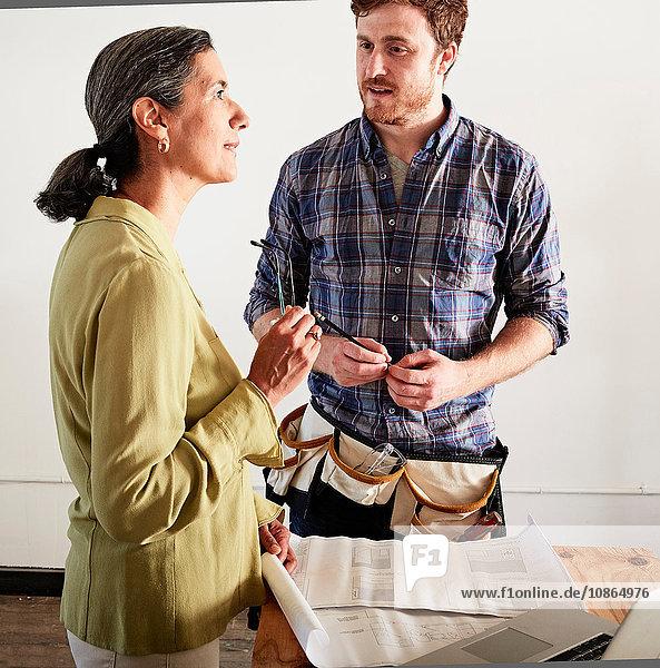 Carpenter and client discussing blueprint