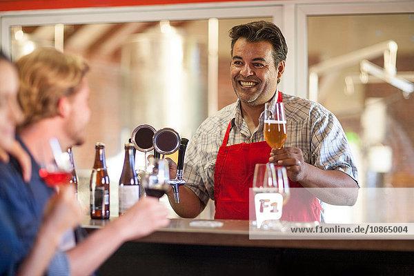 Barkeeper in Gaststätte serviert Kunden Bier lächelnd