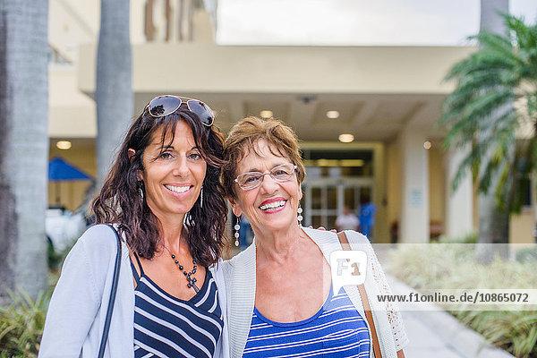 Mutter und erwachsene Tochter schauen lächelnd in die Kamera