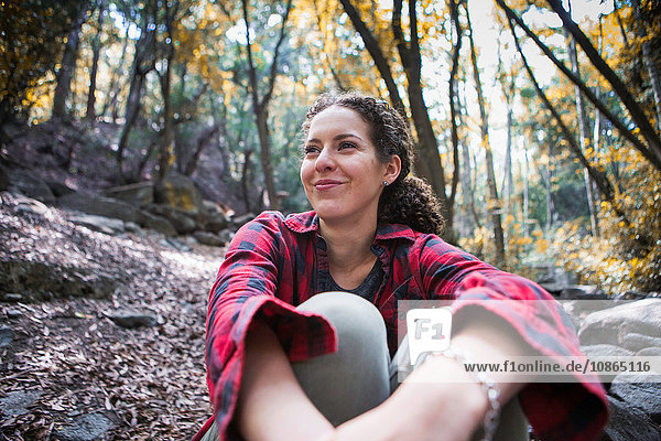 Young female hiker sitting in forest  Arcadia  California  USA