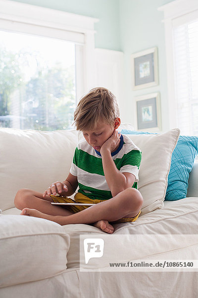 Boy sitting on sofa using digital tablet