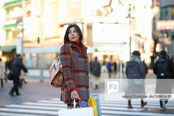 Seitenansicht einer reifen Frau in der Stadt  die Einkaufstaschen trägt und über die Schulter wegschaut  Shibuya  Tokio  Japan