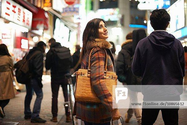 Seitenansicht einer reifen Frau  die nachts in der Stadt eine Handtasche auf der Schulter trägt und lächelnd aufblickt  Shibuya  Tokio  Japan