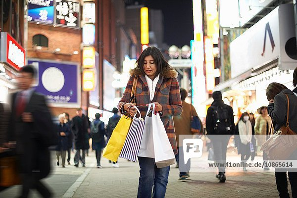 Front view of mature woman carrying shopping bags in city at night looking down,  Shibuya,  Tokyo,  Japan
