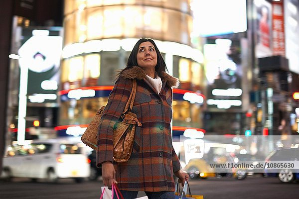 Mature woman carrying shopping bags in city at night looking up  Ginza  Tokyo  Japan