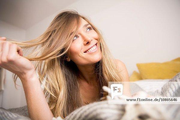 Schöne Frau auf dem Bett liegend mit Hand in langen blonden Haaren