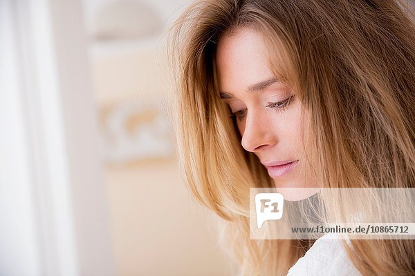 Close up portrait of beautiful woman with long blond hair in living room