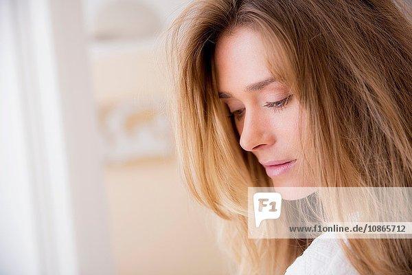 Nahaufnahme eines Porträts einer schönen Frau mit langen blonden Haaren im Wohnzimmer