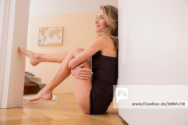 Mittelgroße erwachsene Frau in schwarzer Unterwäsche sitzt in der Tür