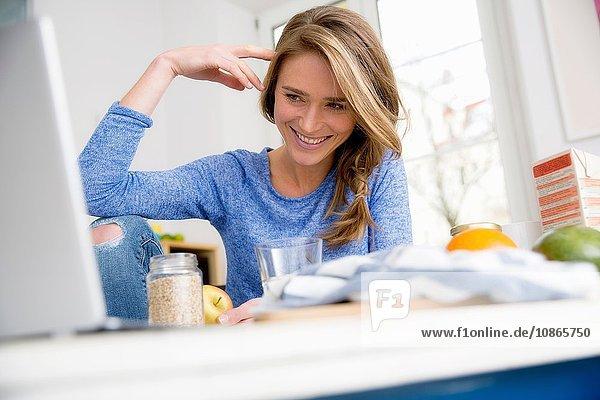 Glückliche Frau sitzt am Küchentisch und stöbert am Laptop