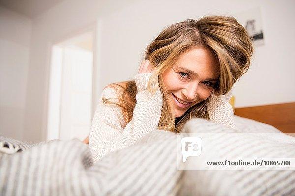 Bildnis einer schönen Frau auf dem Bett liegend mit Händen in langen blonden Haaren