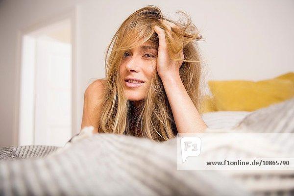 Bildnis einer schönen Frau auf dem Bett liegend mit der Hand in langen blonden Haaren