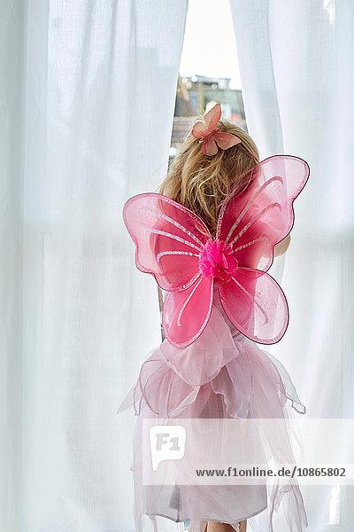 Mädchen in Feenkostüm  das durch den Vorhang schaut Mädchen in Feenkostüm, das durch den Vorhang schaut