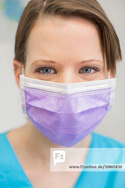 Porträt einer jungen Zahnärztin mit Maske  die in die Kamera schaut