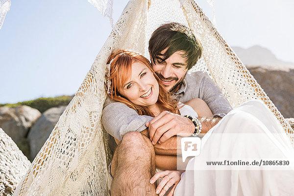 Paar sitzt im Spitzen-Tipi und schaut lächelnd in die Kamera