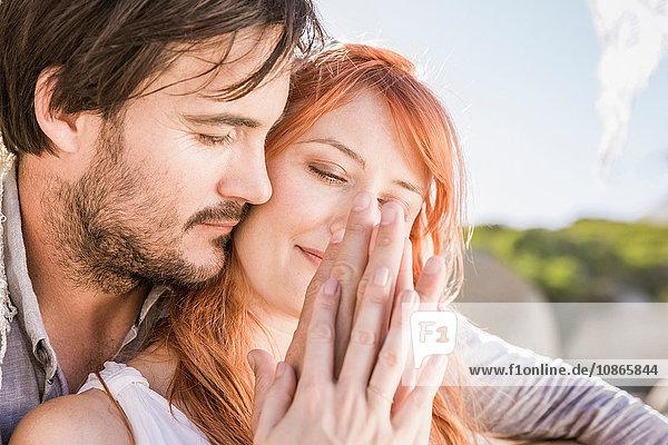 Kopf und Schultern eines Paares  das sich umarmt und liebevoll an den Händen hält
