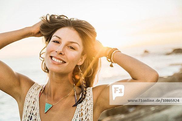 Porträt einer mittleren erwachsenen Frau mit Händen im Haar am Strand bei Sonnenuntergang  Kapstadt  Südafrika