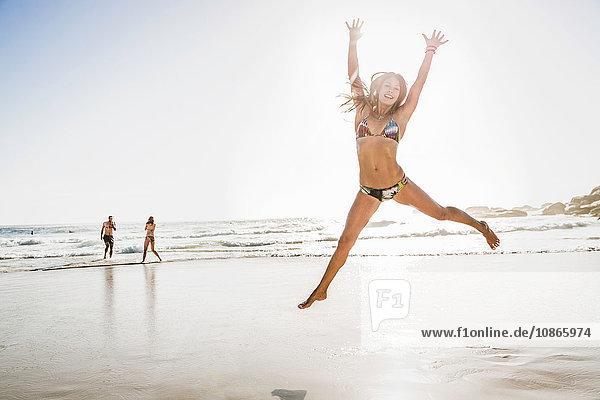 Mittlere erwachsene Frau im Bikini  die am Strand in der Luft herumspringt  Kapstadt  Südafrika